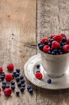Wooden table with assortment berries blueberries and raspberries