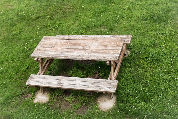 Wooden table with benches for picnic in the shade on green lawn
