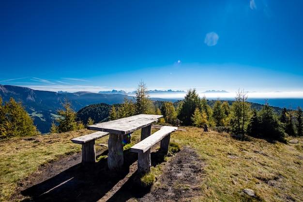 日光の下で緑に覆われたイタリアアルプスに囲まれたベンチ付きの木製テーブル