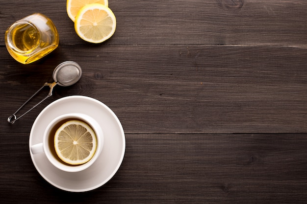 Wooden table with black tea, lemon and honey