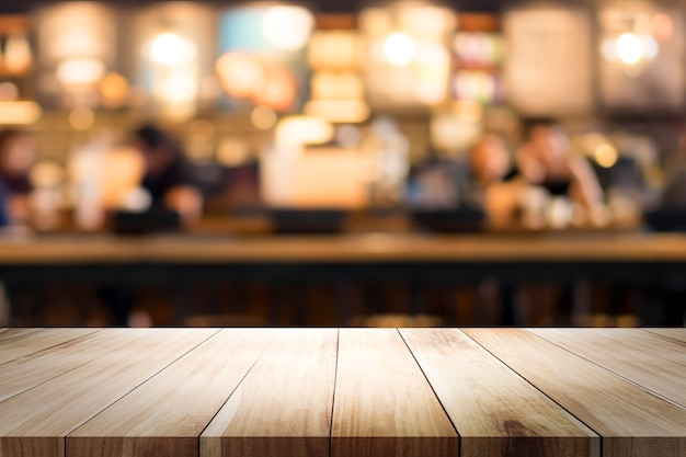Wooden table with blur background of coffee shop.