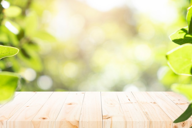 Wooden table with blur background of green bokeh.