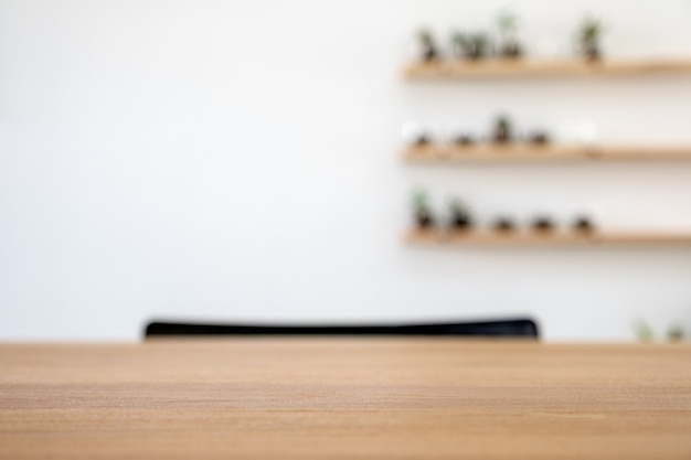Wooden table with blurred white wall background