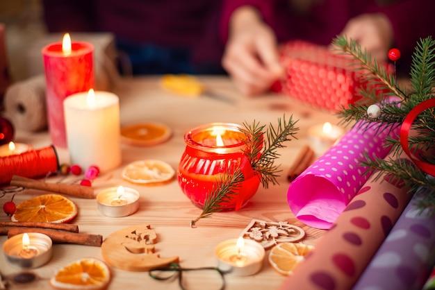 촛불, 말린 오렌지, 계피 스틱 및 포장지가있는 나무 테이블