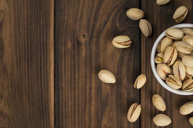 피스타치오로 채워진 세라믹 그릇이있는 나무 테이블. 단백질과 탄수화물의 천연 공급원입니다.