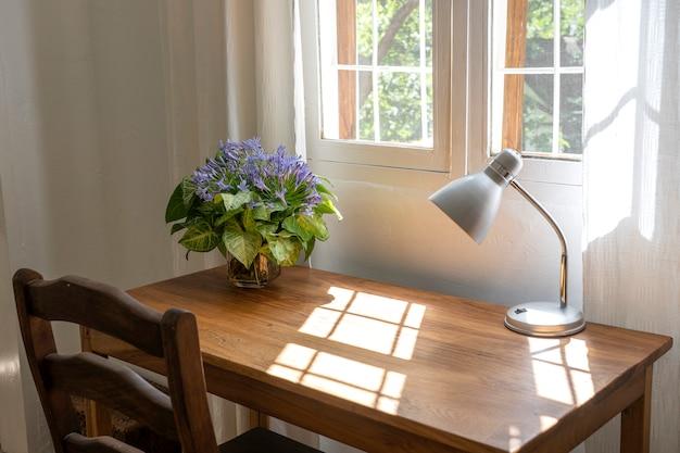 의자, 램프 및 집에서 현대적인 작업 영역의 창 근처에 꽃의 꽃다발 나무 테이블