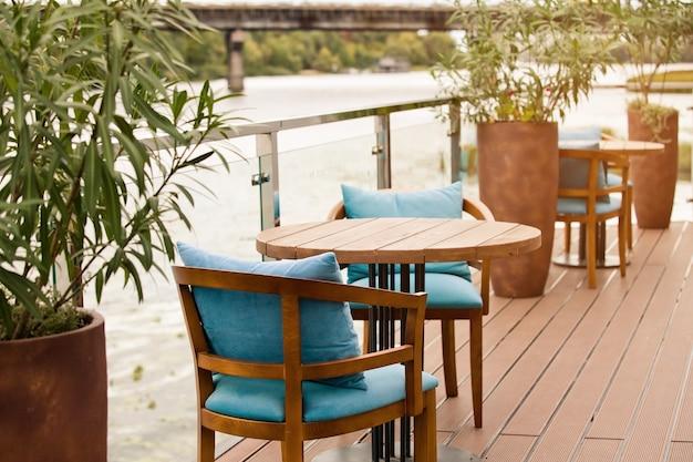 Деревянный стол со стульями на пристани с видом на реку