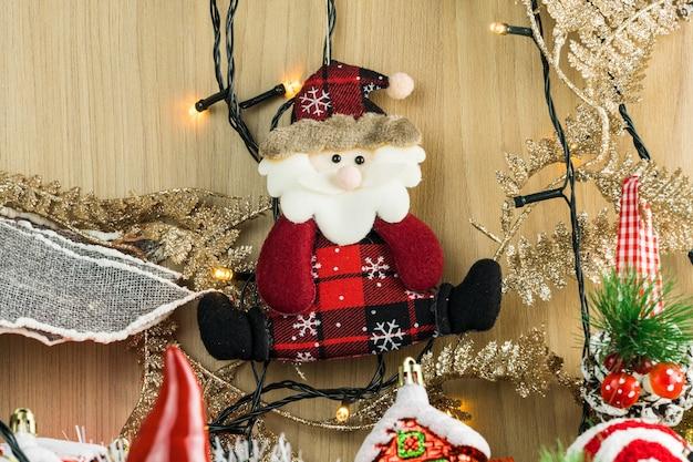 Деревянный стол с елочными украшениями. красные, серебряные и золотые шары, подарочные коробки, фонари, дед мороз, панеттоне, елка и другие. выборочный фокус.
