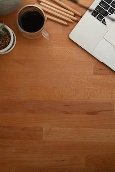 Деревянный стол с чашкой кофе и ноутбуком