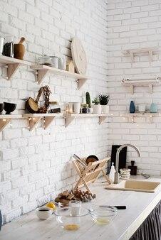 白い素朴なキッチンパステルカラーのさまざまな台所用品と木製のテーブル