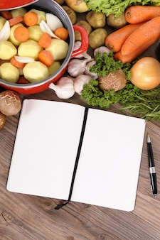 Wooden table with food and notebook