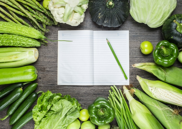 Wooden table with green vegetables and a notebook