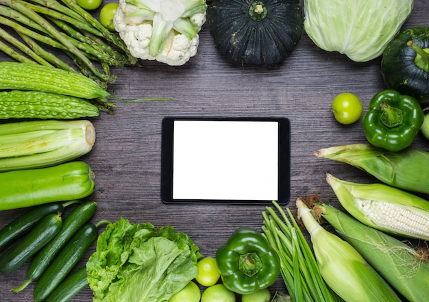 Wooden table with green vegetables and a tablet