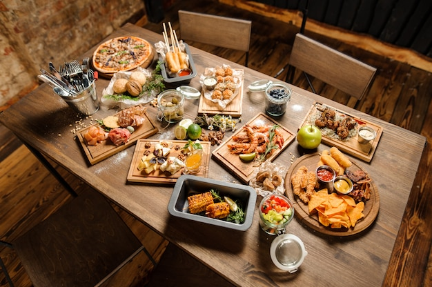 Wooden table with a large amount of tasty dishes