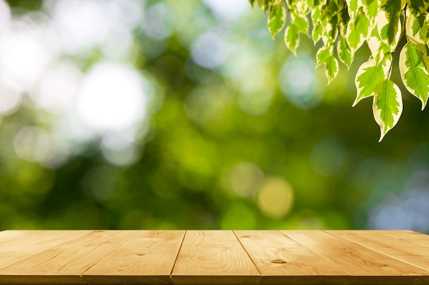 The wooden table with leaves on nature background and copy space for insert text.