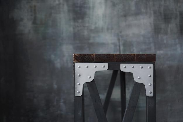 Деревянный стол с металлическими вставками. стол в стиле лофт на фоне темной стены в стиле гранж и лофт