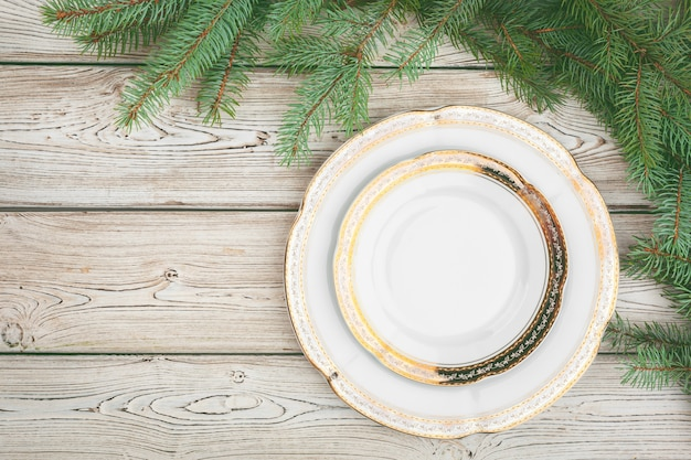 Wooden table with pine tree branches and holiday table setting