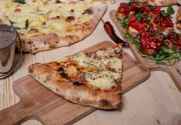 ピザのスライスと典型的なナポリのブルスケッタの木製テーブル。孤立した画像