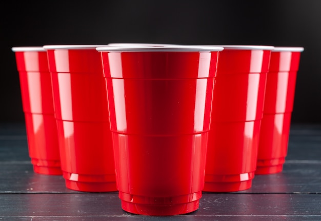Wooden table with red cups and ball for beer pong