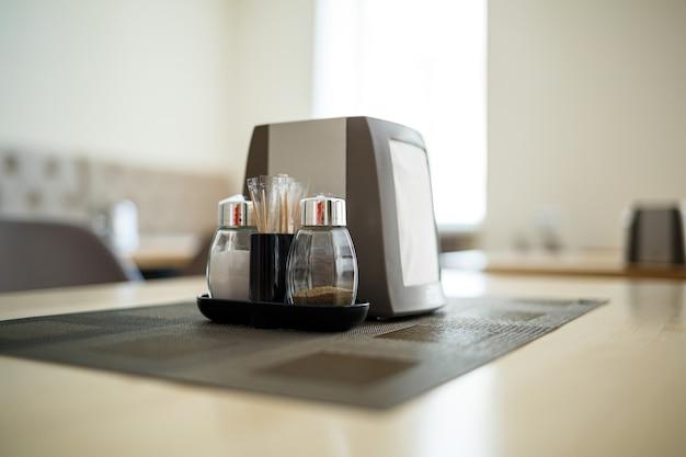 Деревянный стол с сервировкой, солью и перцем, салфетница, чашка черного кофе.