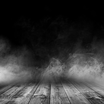 Wooden table with smoke and black background