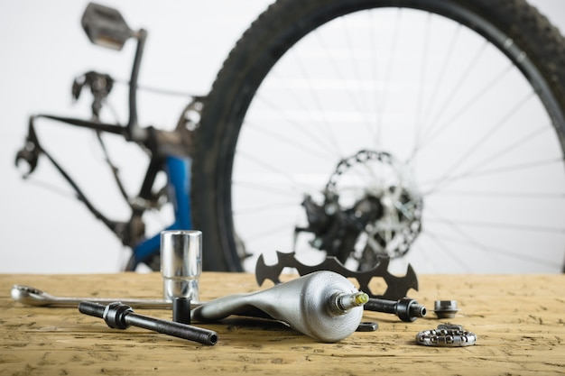 Wooden table with spare parts for mountain bike.