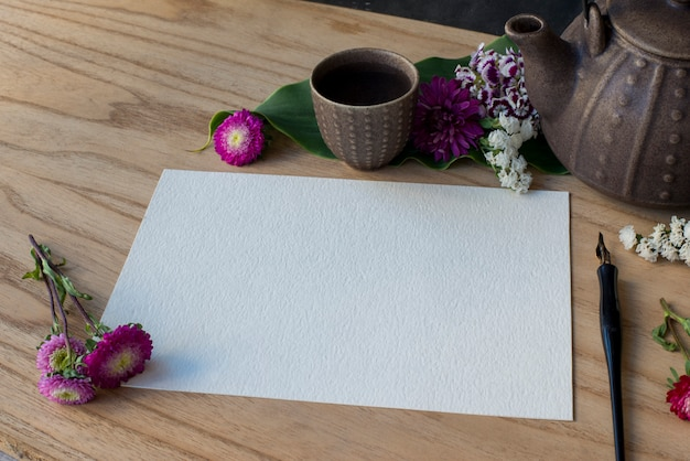 Wooden table with teapot and tea cups with floral arrangements and personal notebook