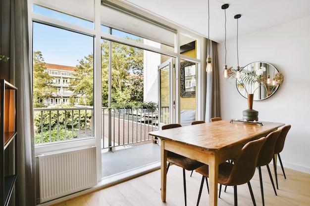 Деревянный стол с вазой и стульями возле открытой балконной двери в светлой столовой дома