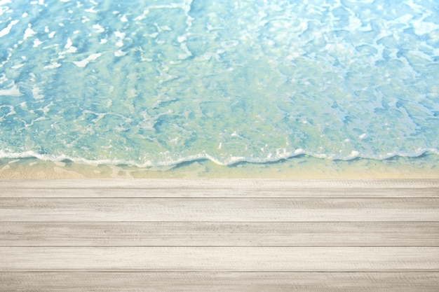 해변에 물결이 있는 나무 테이블