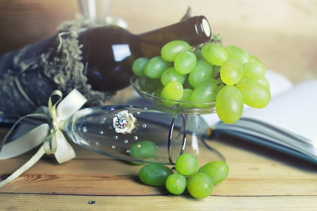 Wooden table with wine bottle book and grape