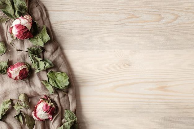 ベージュの布に枯れた花と木製のテーブル