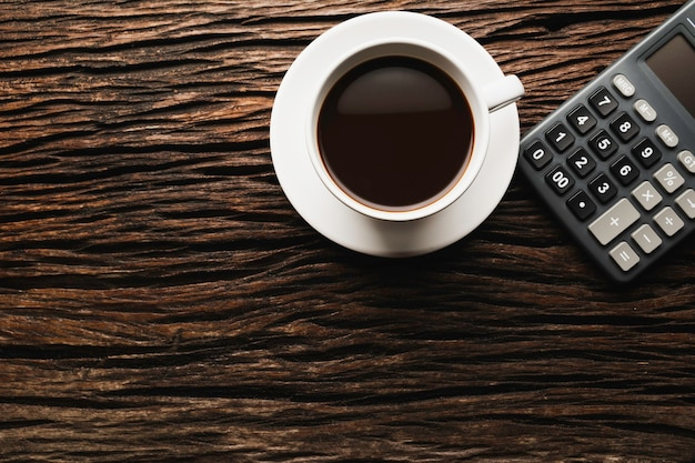 Wooden table wooden desk with coffee and calculator. top view of coffee cup on wooden background with copy space.