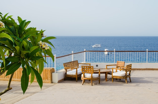 Wooden tables and chairs on terrace of cozy summer cafe overlooking sea.