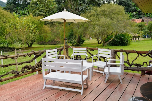 Wooden tables, white chairs in the garden.