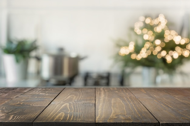 Wooden tabletop and blurred kitchen decorated christmas tree.