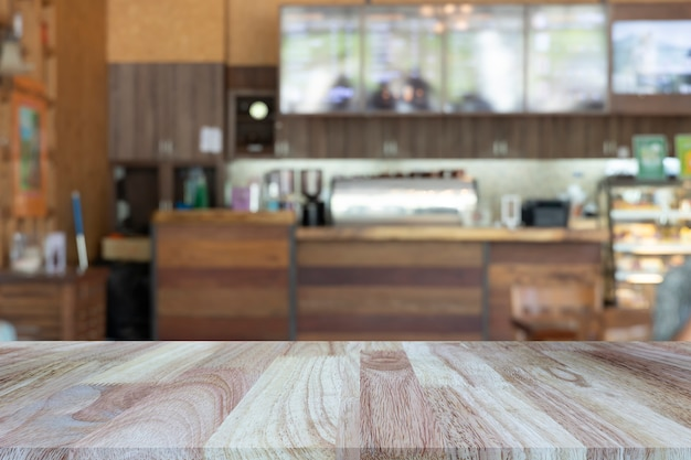 Wooden tabletop on blurred restaurant or coffee shop background.