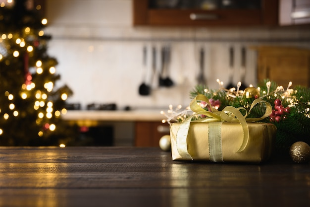 Wooden tabletop with gold gift christmas decoration and blurred modern kitchen for display or montage your products.