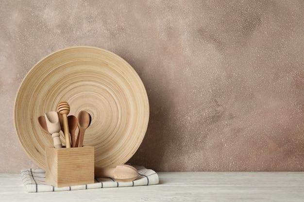 Деревянная посуда и столовые приборы на белом столе на коричневом фоне