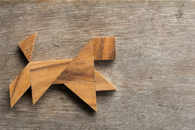 Wooden tangram as running dog shape on old wood background