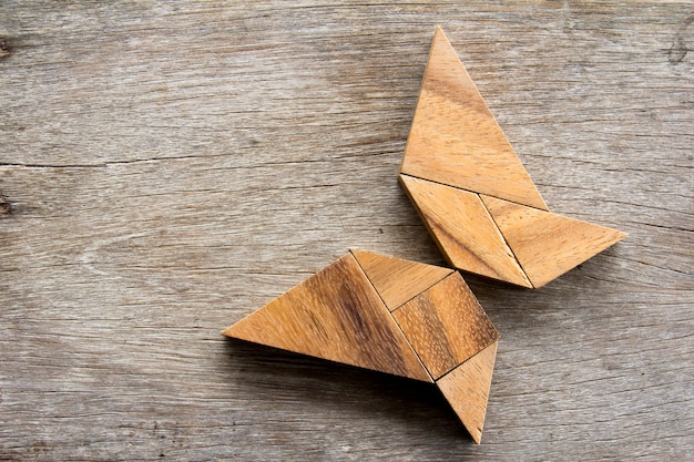 Wooden tangram puzzle in flying butterfly shape background