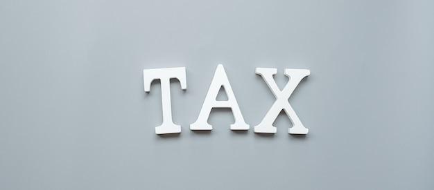 회색에 나무 세금 텍스트입니다. 투자, 납세 시간, 재무, 관리, 비즈니스 및 경제 개념