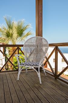ヴィンテージの椅子と海の景色を望むホリデーヴィラまたはホテルの木製テラス