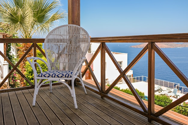 ヴィンテージの椅子と海の景色を望むホテルの木製テラス。