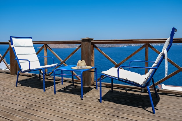 Деревянная терраса виллы или отеля с двумя белыми стульями и столом и видом на море
