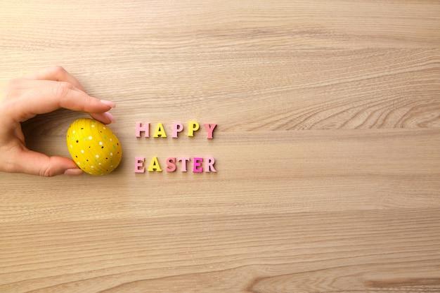 Деревянный текст счастливой пасхи и желтое деревянное яйцо на деревянном столе