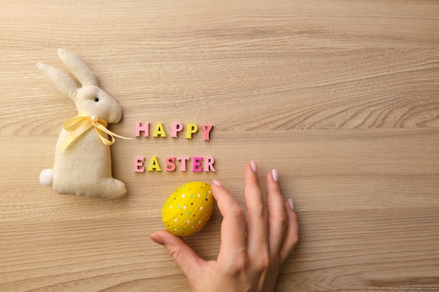 Деревянный текст счастливой пасхи на деревянном столе, женская рука с расписным яйцом и кролик ручной работы из ткани