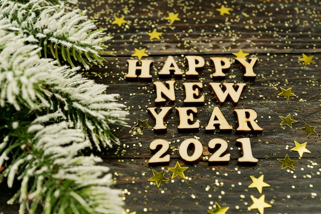 Wooden text and numbers 2021 on wooden with confetti and fur branch
