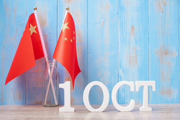 Wooden text of october 1 with with china flags. national day of the people's republic of china, public nation holiday day and happy celebration concepts