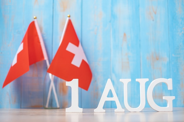 ミニチュアスイスの旗と8月1日の木製のテキスト。スイス建国記念日と幸せなお祝いの概念