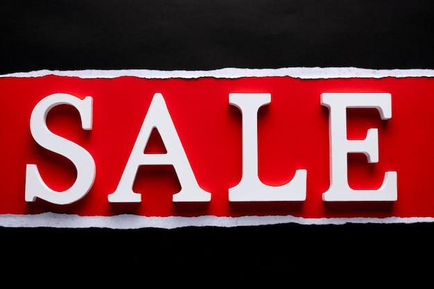Деревянное текстовое слово продажа на черной рваной и красной бумаге.